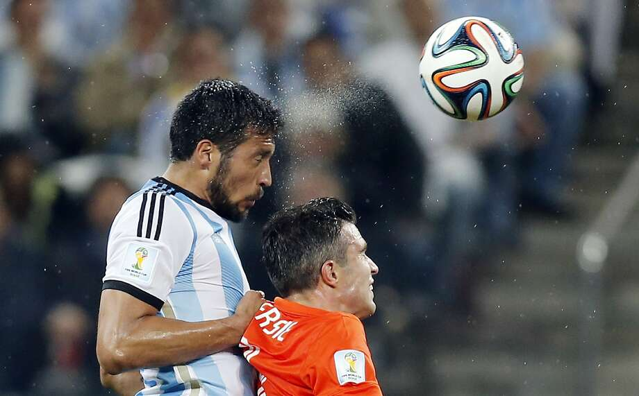 Argentina's Ezequiel Garay, left, and Netherlands' Robin van Persie go for a header during the World Cup semifinal soccer match between the Netherlands and Argentina at the Itaquerao Stadium in Sao Paulo, Brazil, Wednesday, July 9, 2014.  Photo: Frank Augstein, Associated Press