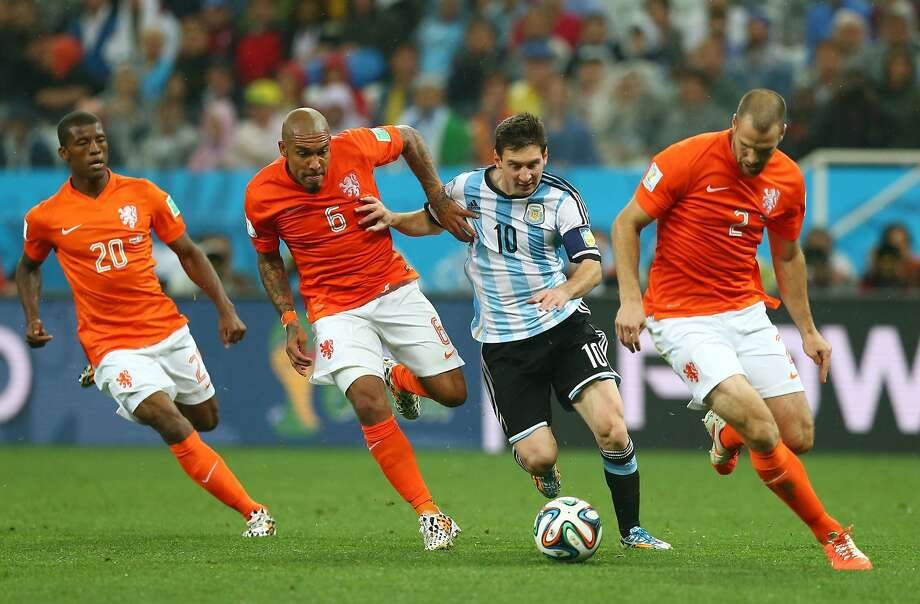 Lionel Messi of Argentina controls the ball as (L-R) Georginio Wijnaldum, Nigel de Jong and Ron Vlaar give chase during the 2014 FIFA World Cup Brazil Semi Final match between the Netherlands and Argentina at Arena de Sao Paulo on July 9, 2014 in Sao Paulo, Brazil. Photo: Ronald Martinez, Getty Images