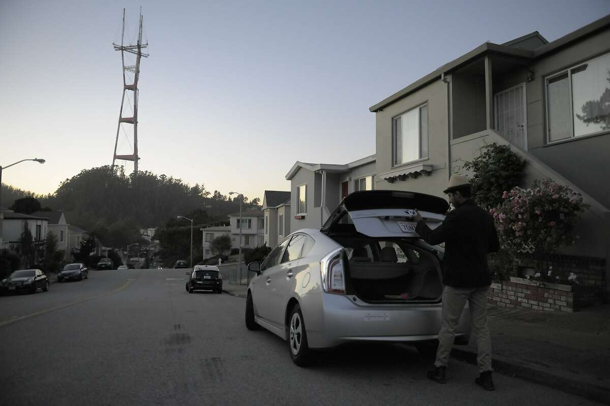 Mohamed Chaoua opens the trunk of his vehicle near his home on June 17, 2014 in San Francisco, CA. Chaoua works as a driver for Uber between being a part-time musician and a single dad to a 5 year old daughter.