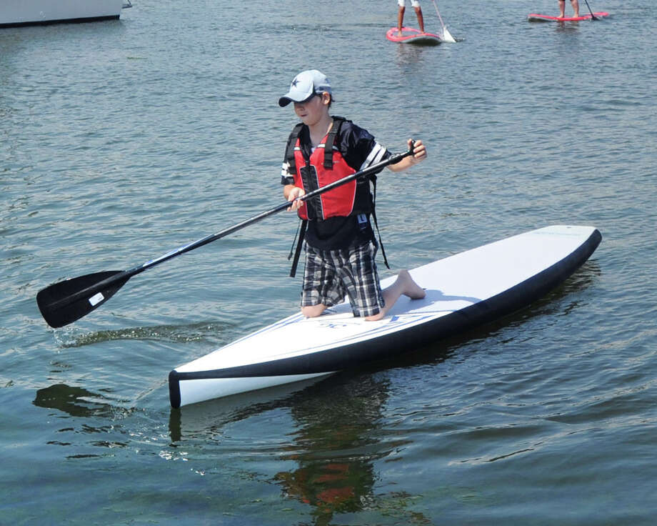 At left, Dennis Murphy, 14, takes part in the Greenwich Teen Center free standup paddle-boarding program in Greenwich Harbor, Wednesday, July 9, 2014. Certified instructor Spencer Dinnean led the class. Photo: Bob Luckey / Greenwich Time