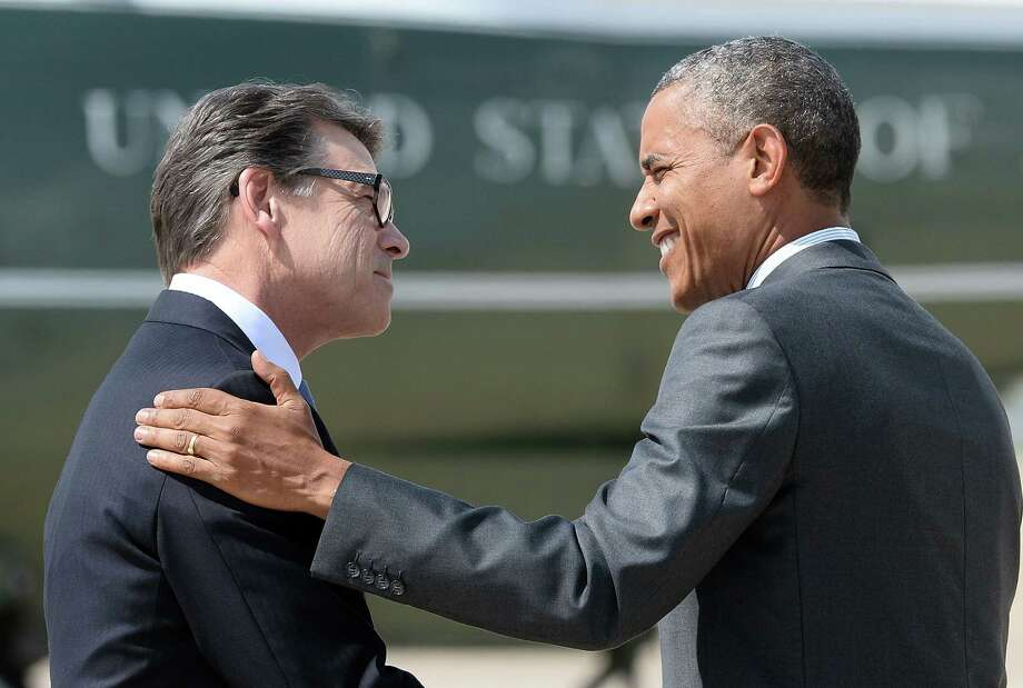 US President Barack Obama is greeted by Texas Governor Rick Perry as he arrives in Dallas, Texas, on July 9, 2014 for a meeting with local elected officials and faith leaders to discuss the urgent humanitarian situation at the Southwest border. Obama on requested $3.7 billion in emergency funding from Congress to help cope with a surge of unaccompanied child immigrants from Central America. AFP PHOTO/Jewel SamadJEWEL SAMAD/AFP/Getty Images Photo: JEWEL SAMAD, AFP/Getty Images / AFP