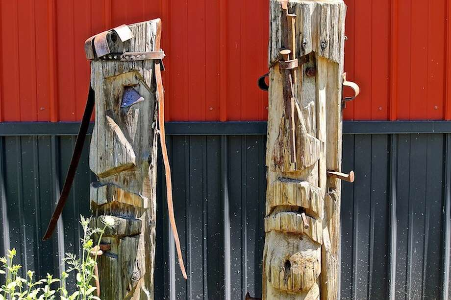 Artist Jason Schultz used a chain saw to create these wooden sculptures out of 125-year-old cedar phone poles. They're on dispay at Wellington's Herbs and Spices in Schoharie. (Christopher Lisio)