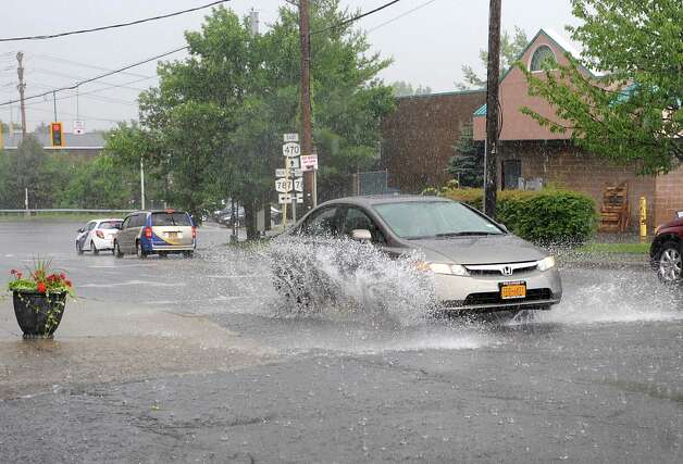 A car splashes though the intersection of Ontario and Saratoga Streets during a thunderstorm on Wednesday, July 9, 2014 in Cohoes, N.Y.  (Lori Van Buren / Times Union) Photo: Lori Van Buren