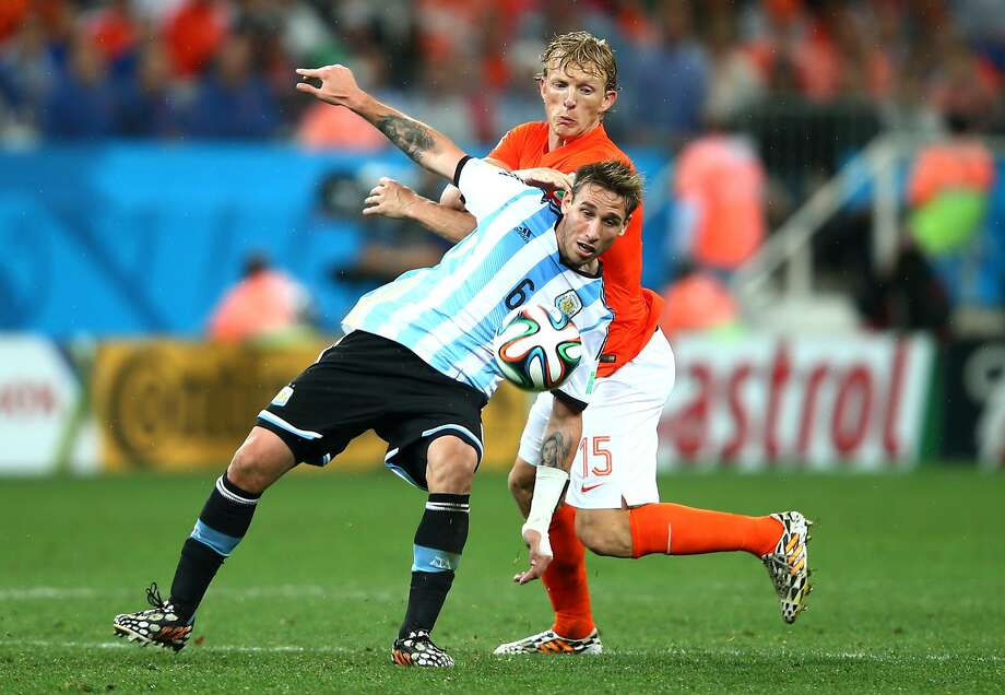 Lucas Biglia of Argentina is challenged by Dirk Kuyt of the Netherlands during the 2014 FIFA World Cup Brazil Semi Final match between the Netherlands and Argentina at Arena de Sao Paulo on July 9, 2014 in Sao Paulo, Brazil.  Photo: Clive Rose, Getty Images