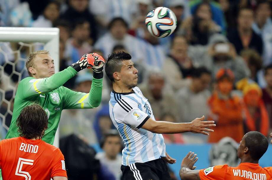 Netherlands' goalkeeper Jasper Cillessen, left, and Argentina's Sergio Aguero challenge for the ball during the World Cup semifinal soccer match between the Netherlands and Argentina at the Itaquerao Stadium in Sao Paulo, Brazil, Wednesday, July 9, 2014.  Photo: Frank Augstein, Associated Press
