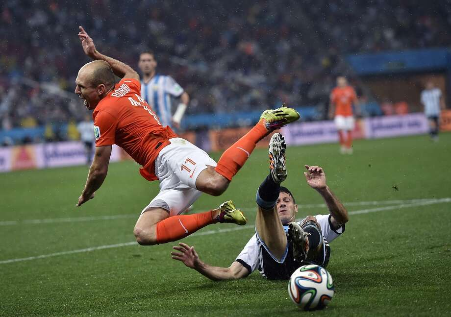 Netherlands' Arjen Robben goes down under a challenge from Argentina's Martin Demichelis during the World Cup semifinal soccer match between the Netherlands and Argentina at the Itaquerao Stadium in Sao Paulo Brazil, Wednesday, July 9, 2014.  Photo: Martin Meissner, Associated Press