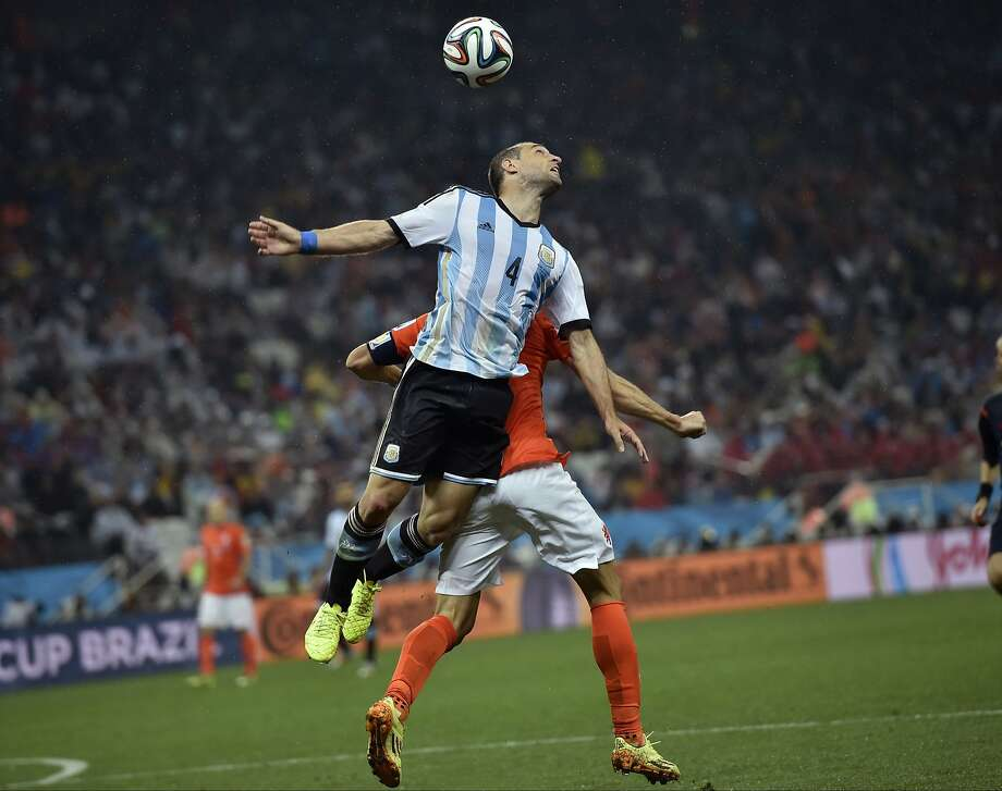 Argentina's Pablo Zabaleta wins a header over Netherlands' Robin van Persie during the World Cup semifinal soccer match between the Netherlands and Argentina at the Itaquerao Stadium in Sao Paulo Brazil, Wednesday, July 9, 2014.  Photo: Martin Meissner, Associated Press