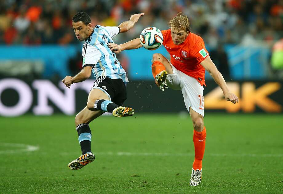Maxi Rodriguez of Argentina and Dirk Kuyt of the Netherlands compete for the ball during the 2014 FIFA World Cup Brazil Semi Final match between the Netherlands and Argentina at Arena de Sao Paulo on July 9, 2014 in Sao Paulo, Brazil.  Photo: Clive Rose, Getty Images