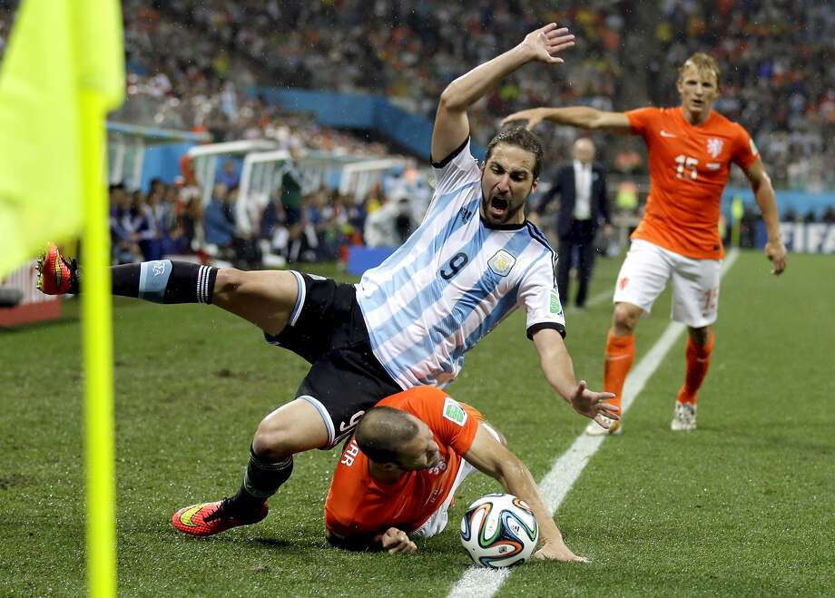Argentina's Gonzalo Higuain (9) falls on top of Netherlands' Ron Vlaar after they collided near the corner during the World Cup semifinal soccer match between the Netherlands and Argentina at the Itaquerao Stadium in Sao Paulo Brazil, Wednesday, July 9, 2014.  Photo: Natacha Pisarenko, Associated Press