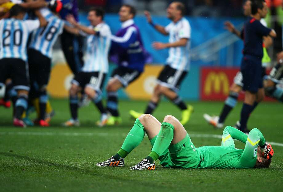 Goalkeeper Jasper Cillessen of the Netherlands reacts after being defeated by Argentina in a penalty shootout as Argentina celebrates during the 2014 FIFA World Cup Brazil Semi Final match between the Netherlands and Argentina at Arena de Sao Paulo on July 9, 2014 in Sao Paulo, Brazil.  Photo: Clive Rose, Getty Images