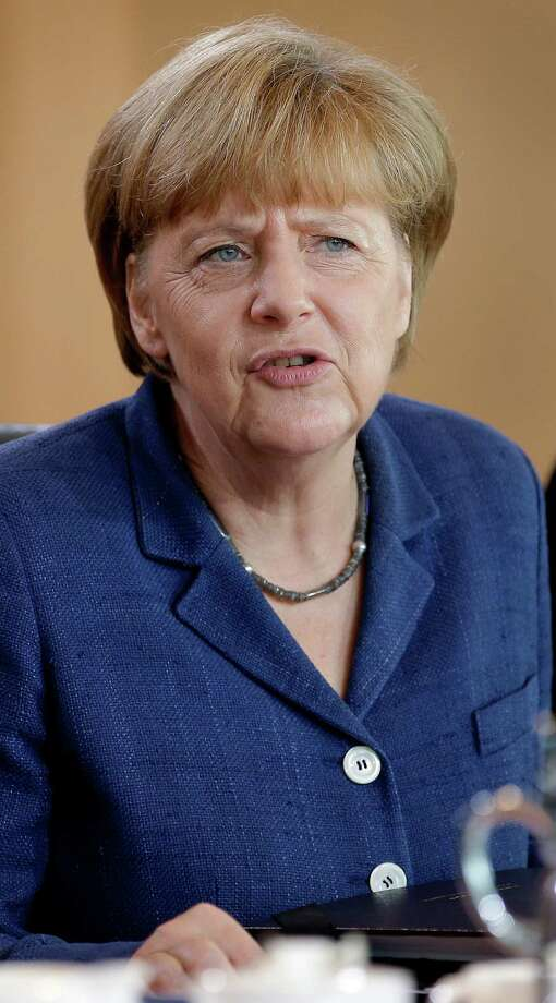 German Chancellor Angela Merkel speaks as she arrives for the weekly cabinet meeting at the chancellery in Berlin, Germany, Wednesday, July 9, 2014. (AP Photo/Michael Sohn) Photo: Michael Sohn, STF / AP