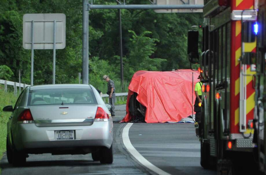 Tarp drapes a vehicle involved in a crash on I-87 South near the Crossgates ramp causing the highway to be closed in that area on Wednesday, July 9, 2014 in Guilderland, N.Y.  (Lori Van Buren / Times Union) Photo: Lori Van Buren
