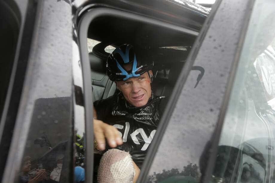 A battered Christopher Froome of Britain gets a ride out of the Tour de France, which he won last year. Photo: Laurent Cipriani, Associated Press