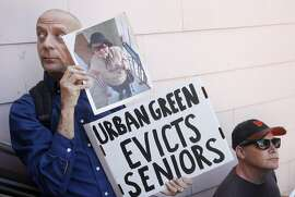 "Ron Winter, left, holds a photo of his 98-year-old neighbor Mary Phillips, who is in the process of being evicted from her home, during a protest organized by Eviction Free SF against David McCloskey at his company, Urban Green Investments' San Francisco headquarters July 9, 2014 in San Francisco, Calif. According to Eviction Free SF, the company has used the Ellis Act to evict tenants, including a 98-year-old woman named Mary Phillips. Approximately 30 people showed up with the intent to enter Urban Green Investments and confront them about the recent evictions. The building was closed, however, and protesters made speeches from a nearby balcony until police were called to escort them off of the private property. After they were moved, protesters chanted on the sidewalk for about fifteen minutes, vowing to return. ""Ask politely,"" said 'fellow evictee' Benito Santiago, ""if that doesn't work, sound off."""