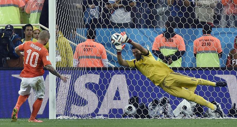 Argentina goalkeeper Sergio Romero makes a save on a penalty kick from the Netherlands' Wesley Sneijder in the shootout, which Argentina won 4-2. Photo: Martin Meissner, Associated Press