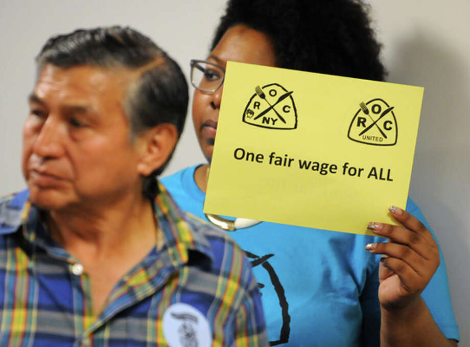 People hold signs as advocates urge Gov. Cuomo to raise the minimum wage for the state's tipped sub-minimum wage, low-wage tipped workers during a press conference at the Legislative Office Building on Wednesday, July 9, 2014 in Albany, N.Y.  (Lori Van Buren / Times Union) Photo: Lori Van Buren, Albany Times Union / 00027720A