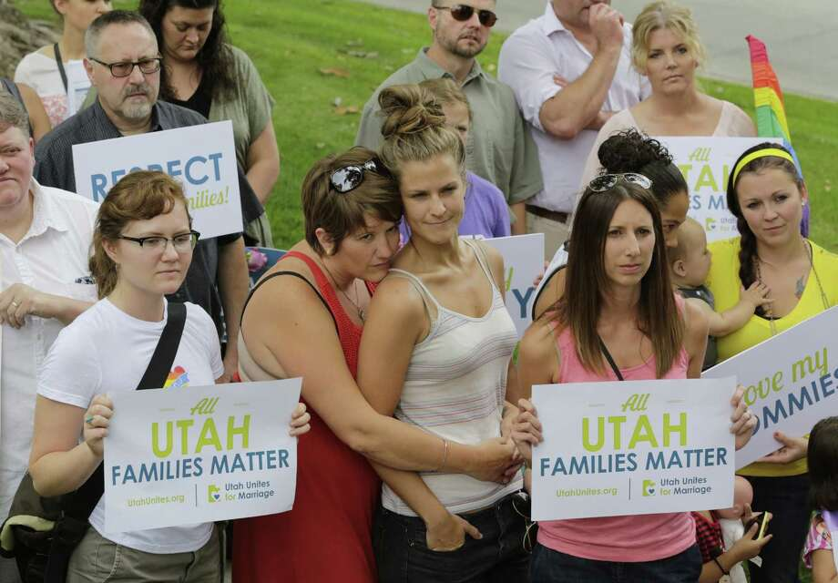 People look on as they gather with about 50 same-sex marriage advocates while delivering a petition with thousands signatures to the governor's mansion pushing for recognition of gay married couples Wednesday, July 9, 2014, in Salt Lake City. Outside the mansion, gay couples said they should receive the same benefits as others in Utah. The group included a handful of families whose children helped to dump the letters into a cardboard box received by state aides. (AP Photo/Rick Bowmer) Photo: Rick Bowmer, STF / AP