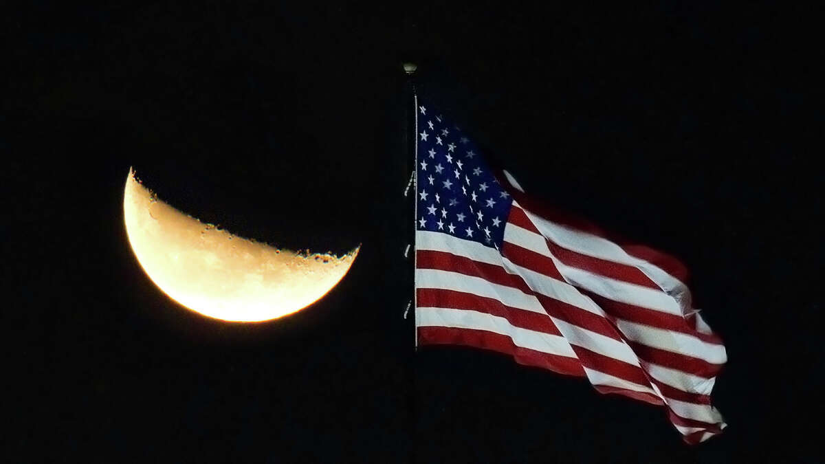A waning crescent moon rises over the stars and stripes at Allen Samuels Dodge on the Katy Freeway near Mason Rd. in the early morning hours of Saturday, Oct. 2, 2010, in Houston.
