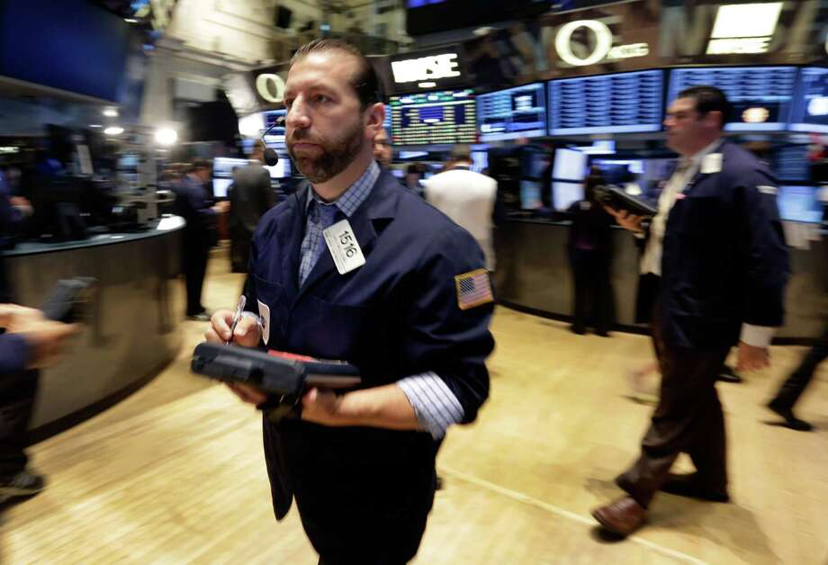 Trader Greg Mulligan, left, works on the floor of the New York Stock Exchange Wednesday, July 9, 2014.  Stocks inched higher in early trading Wednesday, reversing a two-day decline, as the quarterly earnings season got underway with some positive news from the giant aluminum company Alcoa. (AP Photo/Richard Drew) ORG XMIT: NYRD105 Photo: Richard Drew / AP