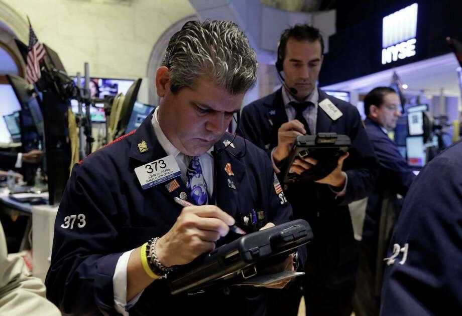 Trader John Panin, left, works on the floor of the New York Stock Exchange. (AP Photo/Richard Drew) Photo: Richard Drew / AP