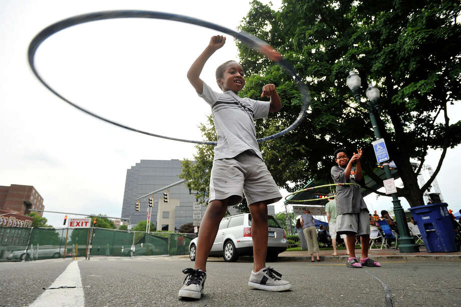 Jahsir Cobb, left, and his friend, Demarcus Bennett, spin Hula Hoops in the street during Jazz Up July at Columbus Park in Stamford, Conn., on Wednesday, July 9, 2014. Hearst Connecticut Media Group is a sponsor of the event. Photo: Jason Rearick / Stamford Advocate