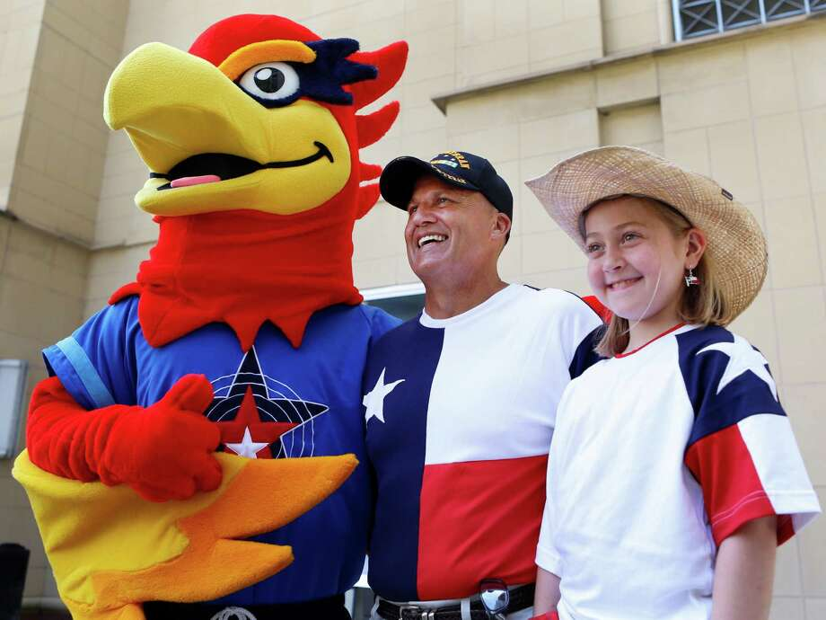 Pete Dodd, center, a heart transplant recipient, and Sydney Kussler, 9, a liver transplant recipient, join mascot Blaze at a Team Texas pep rally Wednesday. Dodd and Kussler will compete in the Transplant Games. Photo: Melissa Phillip, Staff / © 2014  Houston Chronicle