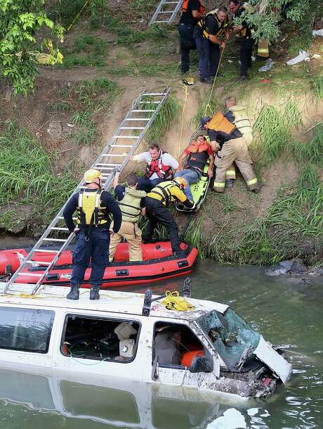 Houston Fire Department personnel work at the scene of a water rescue after a van carrying seven men plunged into White Oak Bayou at Cavalcade and I-45 North. Photo: James Nielsen, Staff / © 2014  Houston Chronicle