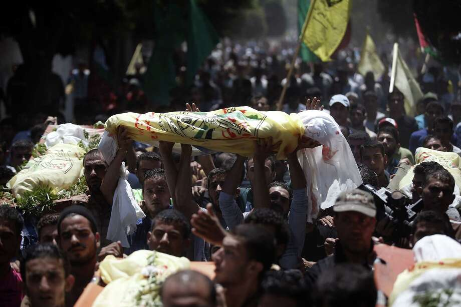 Mourners carry the bodies of a man and his six sons Wednesday during their funeral in the Gaza Strip. The seven died the day before in an Israeli air strike. Photo: THOMAS COEX, Staff / AFP