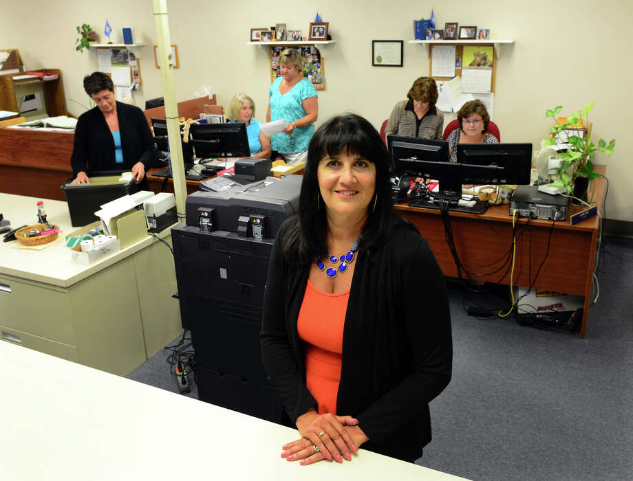 Newly hired Milford City Clerk Joanne Rohrig poses at the City Clerk's Office inside the Parsons Government Center in Milford, Conn. on Wednesday July 9, 2014. Rohrig's staff in the background from left to right is: Suzanne Horvath, Bonnie Kulenych, Bonnie Peloso, Rose Elliott, and Laura Hunt. Photo: Christian Abraham / Connecticut Post