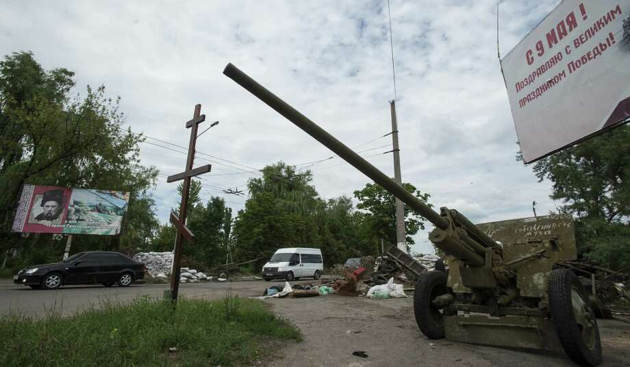 Cars pass an empty pro-Russian checkpoint after heavy fighting between pro-Russian fighters and Ukrainian government troops outside Slovyansk, eastern Ukraine. Photo: Evgeniy Maloletka, Associated Press / AP