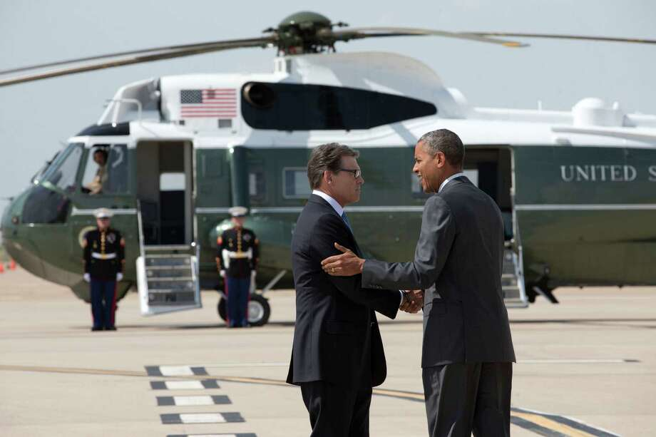 President Barack Obama is greeted by Texas Gov. Rick Perry as he arrives at Dallas/Fort Worth International Airport, Wednesday, July 9, 2014. The president is expected to attend a meeting on immigration, (AP Photo/Jacquelyn Martin) ORG XMIT: TXJM101 Photo: Jacquelyn Martin / AP