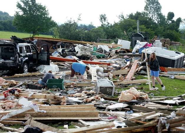 People sort through debris of a destroyed house after Tuesday night's storm, on Wednesday, July 9, 2014, in Smithfield, N.Y. The National Weather Service has confirmed that a tornado destroyed the homes in upstate New York where four people were killed. (AP Photo/Mike Groll) ORG XMIT: NYMG101 Photo: Mike Groll / AP
