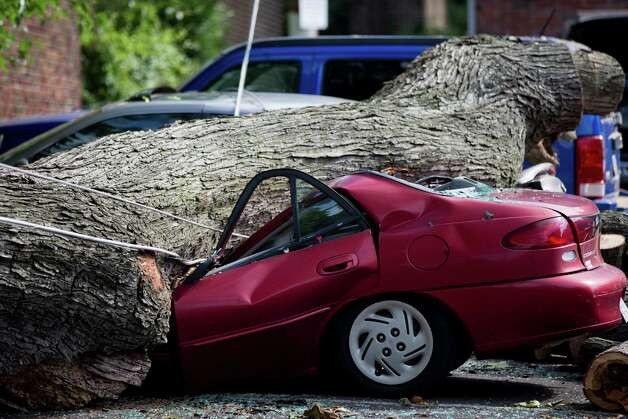 A downed tree lies atop a crushed car Wednesday, July 9, 2014, in Philadelphia. About 228,000 homes and businesses across Pennsylvania remain without power after severe thunderstorms raced across the state. (AP Photo/Matt Rourke) ORG XMIT: PAMR102 Photo: Matt Rourke / AP
