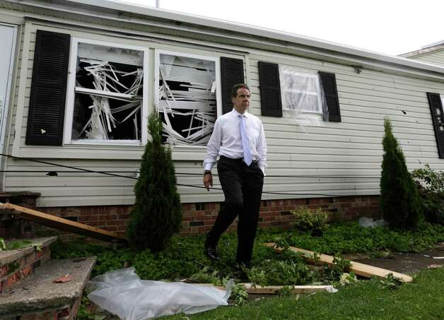 New York Gov. Andrew Cuomo walks near a house that was damaged from Tuesday's storm, on Wednesday, July 9, 2014, in Smithfield, N.Y. The National Weather Service has confirmed that a tornado destroyed the homes in upstate New York where four people were killed. Barbara Watson, the meteorologist leading the agency's survey team says that the violent winds Tuesday were at least 100 mph and reached undetermined higher speeds to cause the damage they're seeing in Smithfield.(AP Photo/Mike Groll) ORG XMIT: NYMG109 Photo: Mike Groll / AP