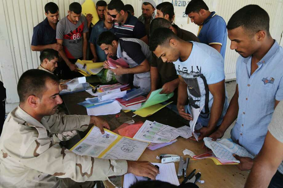 Iraqi men check in at the main army recruiting center as they volunteer for military services in Baghdad. Photo: Karim Kadim / Associated Press / AP