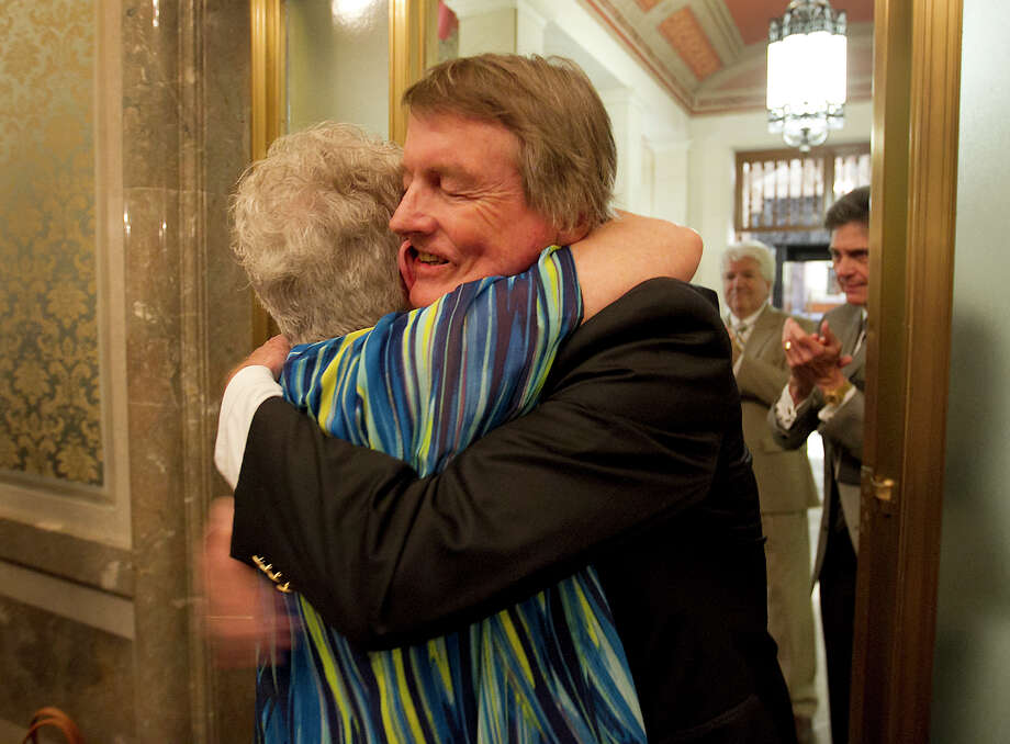 UT-Austin President Bill Powers embraces Martha F. Hilley, a music professor, as he makes an appearance at the Faculty Council on Wednesday. Photo: Ralph Barrera / Austin American-Statesman. State