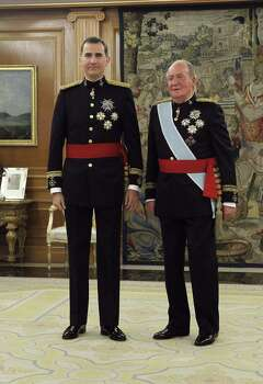 Spain's King Felipe (L) and his father Spain's former King Juan Carlos stand during a handing over ceremony for the sash of the Capitain General in the Chamber of Audiences at the Zarzuela Palace . Spain's King Felipe VI begins a new reign today already facing a threat to the unity of his kingdom as the northeastern region of Catalonia fights to hold an independence referendum on November 9.  AFP PHOTO / pool / ZIPIZipi/AFP/Getty Images Photo: ZIPI, AFP/Getty Images / AFP