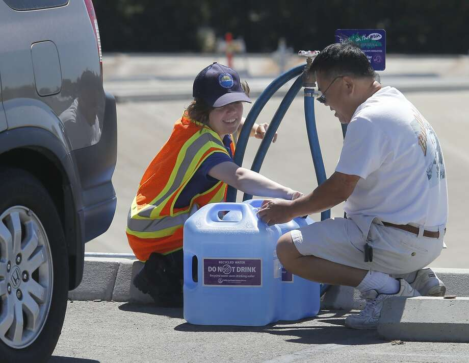 Worker Kristi Kolodzie helps Terry Chi at the water site. Photo: Brant Ward, San Francisco Chronicle