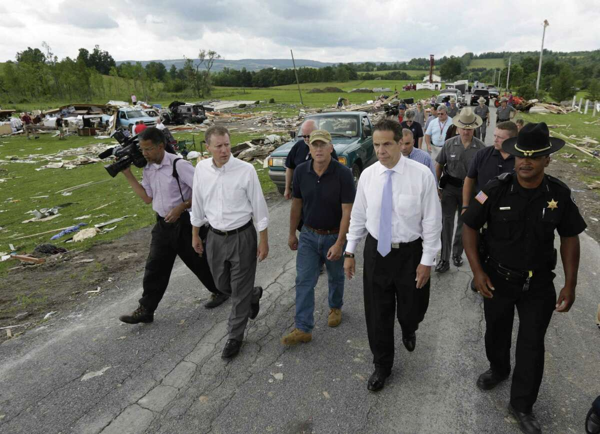 New York Gov. Andrew Cuomo, second from right, walks with state Sen. David Valesky, left, Smithfield Town Supervisor Rick Bargabos and Madison County Sheriff Allen Riley as they survey the damage from Tuesday night's storm, on Wednesday, July 9, 2014, in Smithfield, N.Y. The National Weather Service has confirmed that a tornado destroyed the homes in upstate New York where four people were killed. Barbara Watson, the meteorologist leading the agency's survey team says that the violent winds Tuesday were at least 100 mph and reached undetermined higher speeds to cause the damage they're seeing in Smithfield. (AP Photo/Mike Groll)