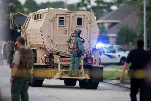 A law enforcement officer rides on the back of an armored vehicle to a standoff with a shooting suspect on Wednesday, July 9, 2014, in Spring. Seven people were shot, with six confirmed dead. Photo: Brett Coomer, Houston Chronicle / © 2014 Houston Chronicle