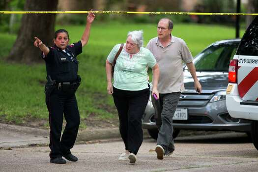 A man and woman are let through the police line to speak with officers following a shooting Wednesday, July 9, 2014, in Spring. Seven people were shot, with six confirmed dead. Photo: Brett Coomer, Houston Chronicle / © 2014 Houston Chronicle