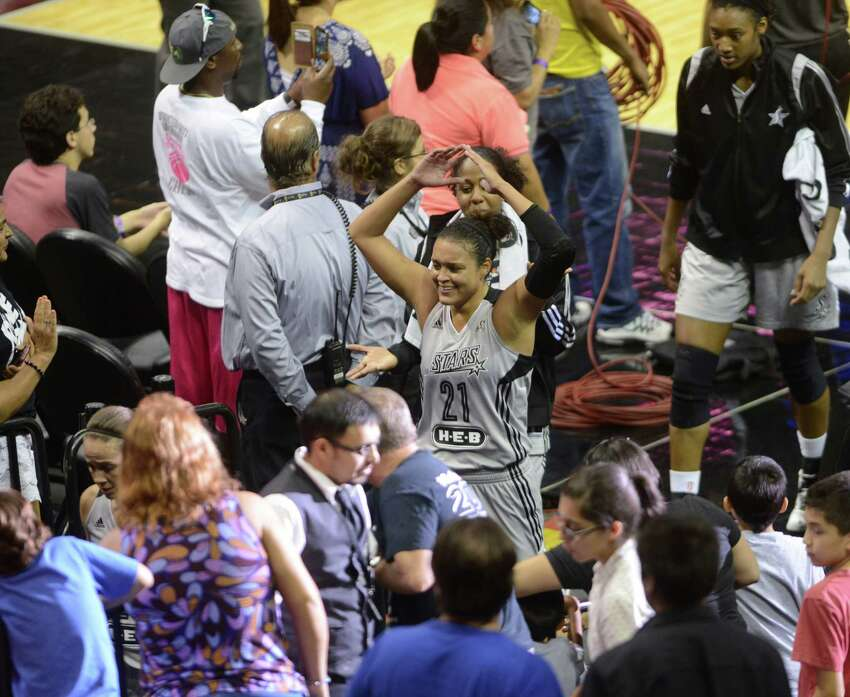 Kayla McBride of the San Antonio Stars greets fans as she leaves the court for halftime during WNBA action against the New York Liberty in the AT&T Center on Wednesday, July 9, 2014.