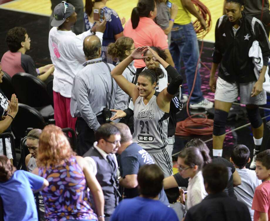 Kayla McBride of the San Antonio Stars greets fans as she leaves the court for halftime during WNBA action against the New York Liberty in the AT&T Center on Wednesday, July 9, 2014. Photo: Billy Calzada, San Antonio Express-News / San Antonio Express-News