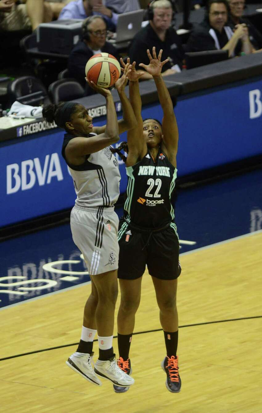 Shameka Christon of the San Antonio Stars, left, shoots as Charde Houston of the New York Liberty defends during WNBA action in the AT&T Center on Wednesday, July 9, 2014.