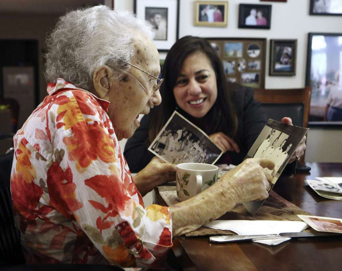 WAAC veteran Lucy Coffey and Queta Marquez go through pictures taken while Coffey was in Japan.