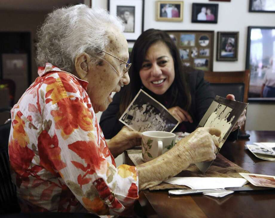 WAAC veteran Lucy Coffey and Queta Marquez go through pictures taken while Coffey was in Japan. Photo: Helen L. Montoya / San Antonio Express-News / SAN ANTONIO EXPRESS-NEWS