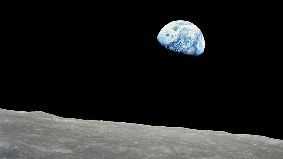 The rising Earth is above the lunar horizon in this telephoto view taken from the Apollo 8 spacecraft.  The crew took the photo around 10:40 a.m. Houston time on the morning of December 24, 1968. Photo: NASA / NASA