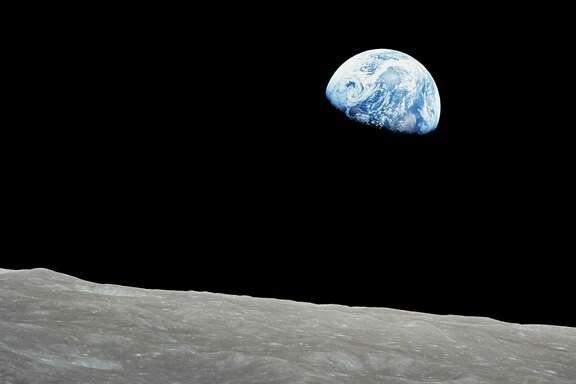 The rising Earth is above the lunar horizon in this telephoto view taken from the Apollo 8 spacecraft.  The crew took the photo around 10:40 a.m. Houston time on the morning of December 24, 1968.