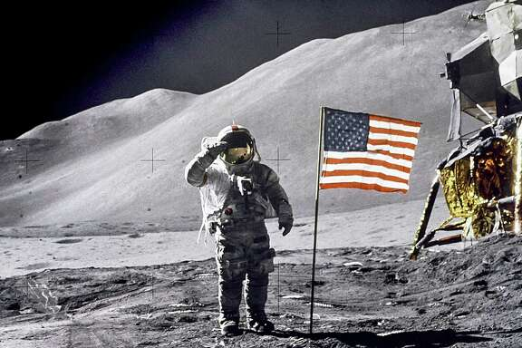 Astronaut David R. Scott gives a military salute while standing beside the U.S. flag during the Apollo 15 lunar surface extravehicular activity at the Hadley-Apennine landing site in 1971.