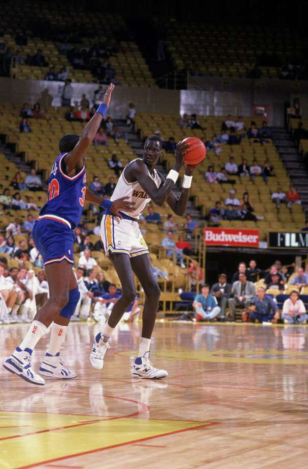 1989:  Manute Bol #11 of the Golden Sate Warriors looks to pass the ball during a game. NOTE TO USER: User expressly acknowledges and agrees that, by downloading and/or using this Photograph, User is consenting to the terms and conditions of the Getty Images License Agreement. Mandatory copyright notice: Copyright 2001 NBAE  Mandatory Credit: Ken Levine/Getty Images Photo: Ken Levine, ST / Getty Images